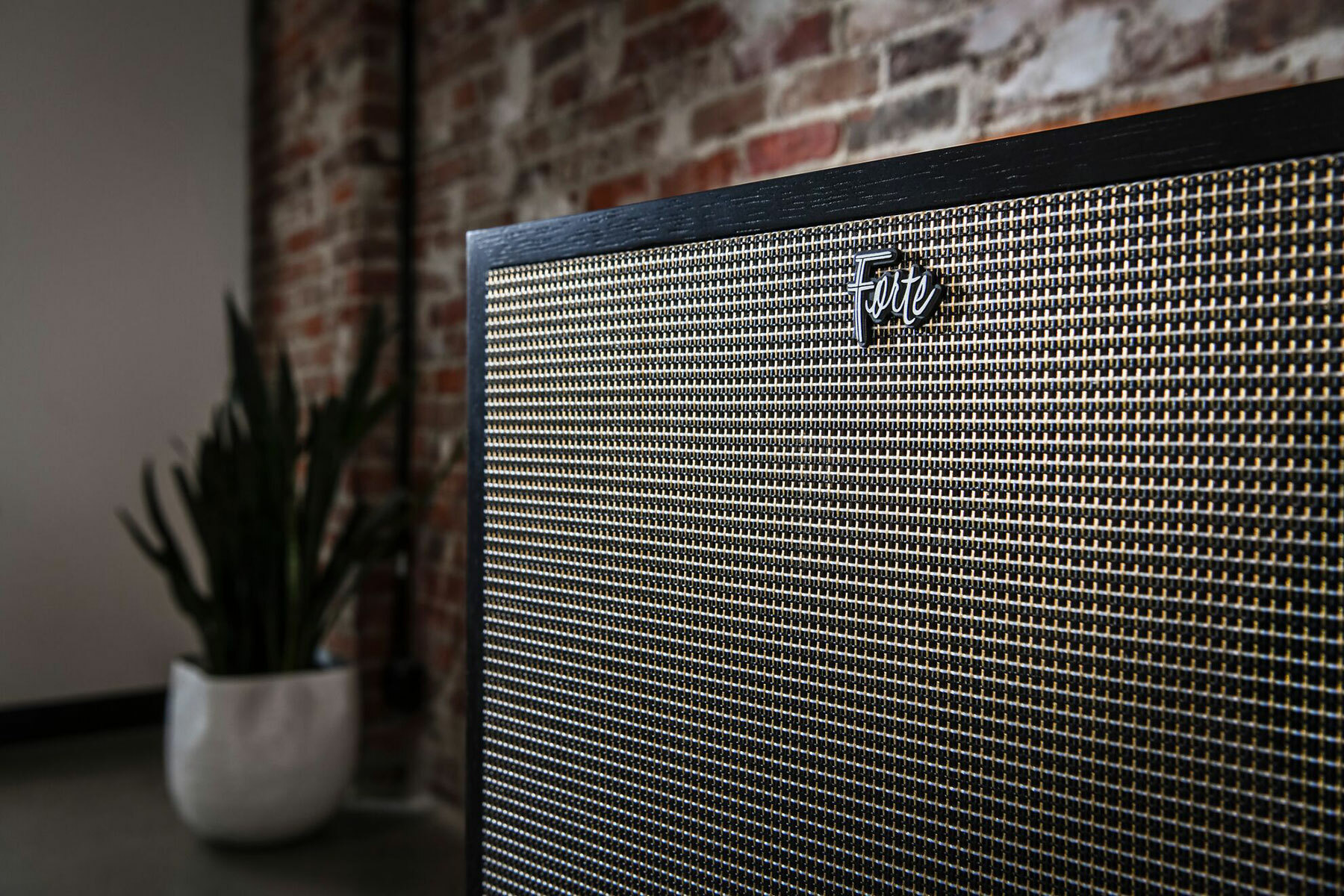 Forte IV black ash loudspeaker with grille up close against a brick wall