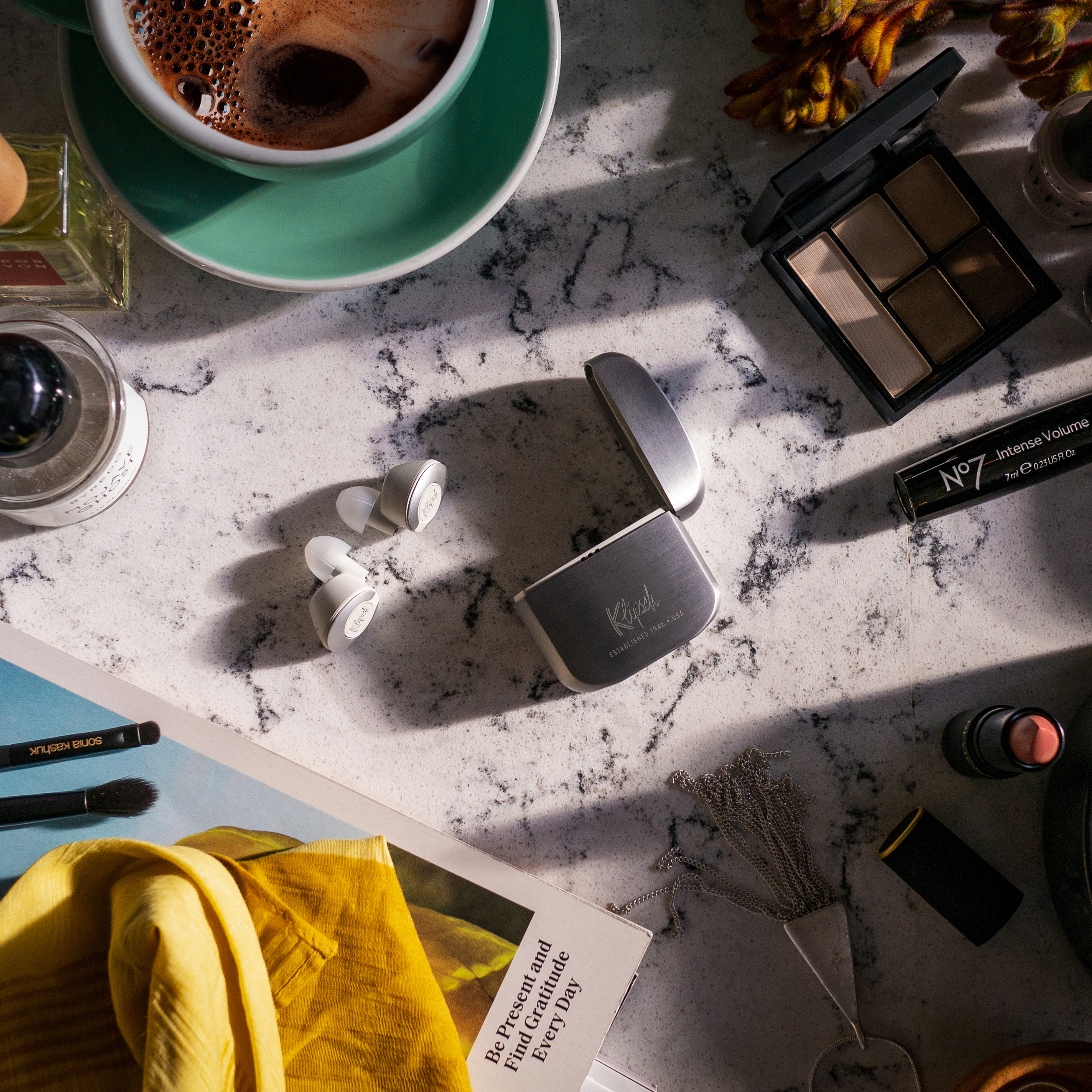 Flatlay of Klipsch T5 II True Wireless earbuds, coffee and some makeup on a marble table